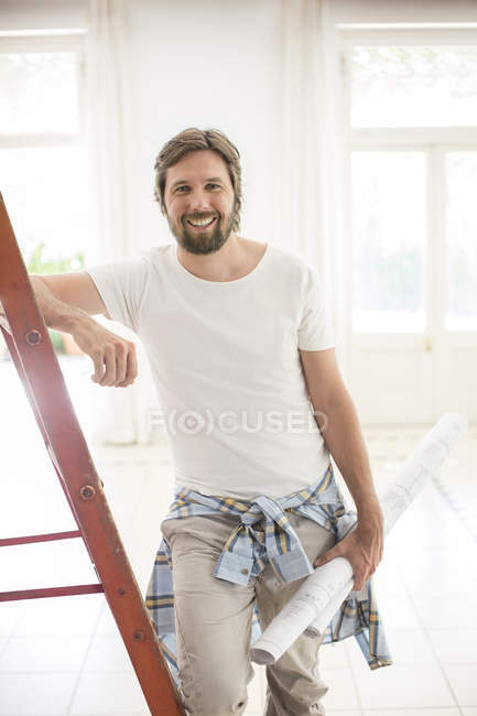 Man standing on ladder in living space — Stock Photo