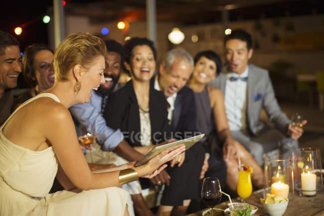Amici che utilizzano tablet digitale alla festa — Foto stock
