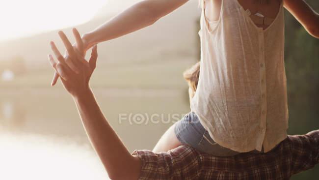 Joven a mujer que lleva sobre los hombros - foto de stock