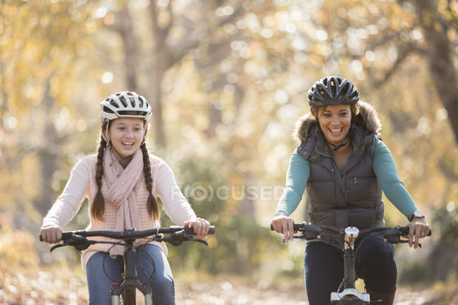 Smiling mother and daughter bike riding outdoors — Stock Photo