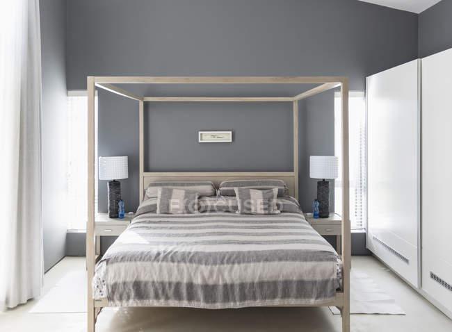 Biancheria da letto a righe sul letto a baldacchino nella camera da letto interna moderna home Vetrina — Foto stock