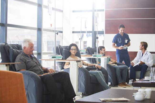 Patients sous traitement médical avec des médecins discutant en clinique externe — Photo de stock