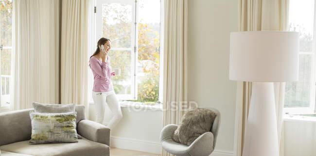 Женщина пьет кофе и разговаривает по мобильному телефону у окна гостиной — стоковое фото