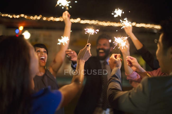 Friends playing with sparklers at party — Stock Photo