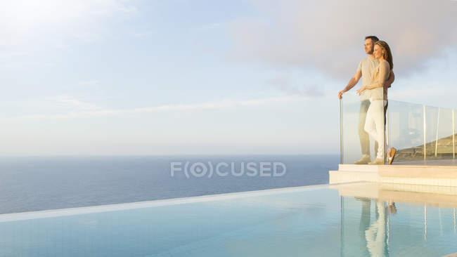 Casal com vista para o oceano a partir da varanda moderna — Fotografia de Stock