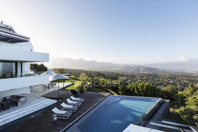 Moderna casa di lusso vetrina esterna con piscina e vista sulle montagne — Foto stock