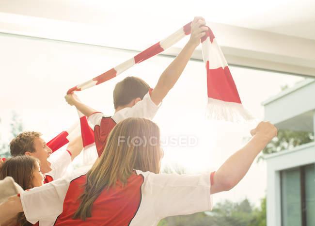 Familie in Sporttrikots Jubel im Wohnzimmer — Stockfoto