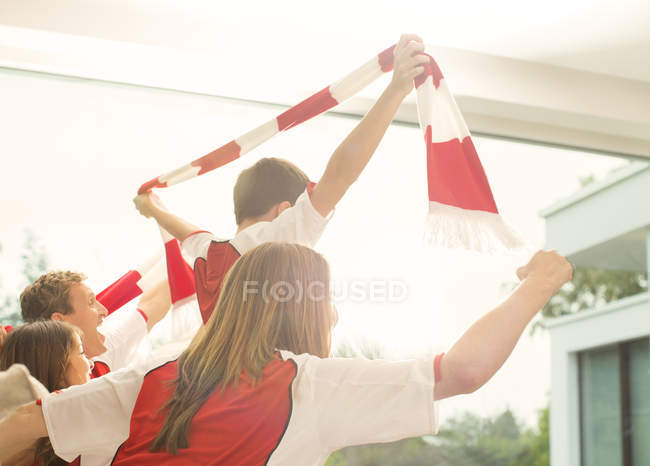 Family in sports jerseys cheering in living room — Stock Photo
