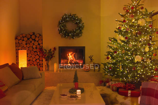 Ambient fireplace and candles in living room with Christmas tree — Stock Photo