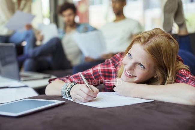 Жінка, писати в офісі лежачи на стіл — стокове фото