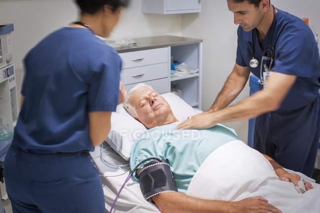 Médico realizando Cpr em paciente inconsciente na sala de emergência — Fotografia de Stock