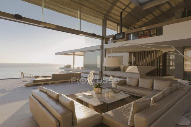 Сонячний сучасні, розкішні будинку Вітрина інтер'єр вітальні відкритим видом на океан — стокове фото