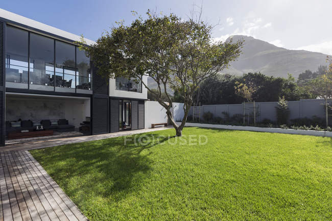 Sunny home showcase exterior lawn and tree below mountain — Stock Photo