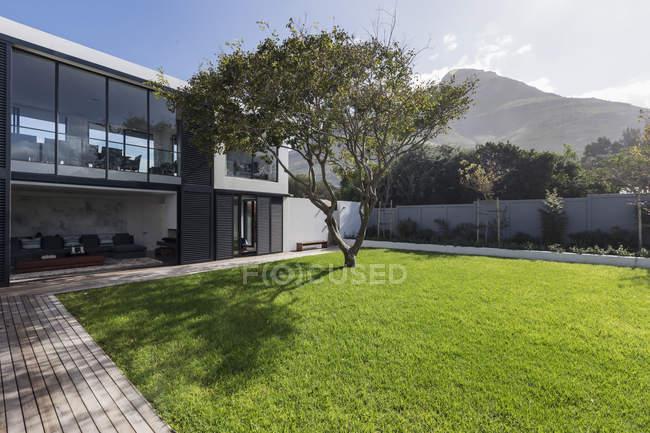 Sunny casa vitrine gramado exterior e árvore abaixo da montanha — Fotografia de Stock