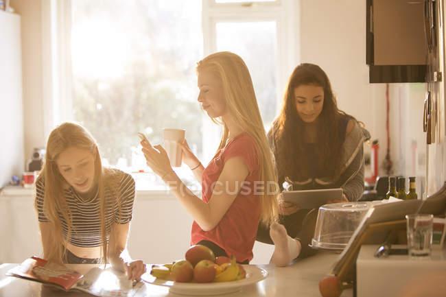 Ragazze adolescenti leggono scomparto, SMS e utilizza la compressa di digital nella cucina — Foto stock