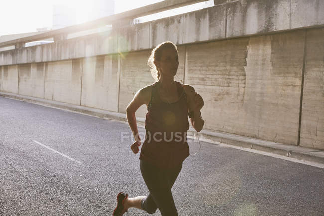 Силуэт бегущая женщина на солнечной городской улице — стоковое фото