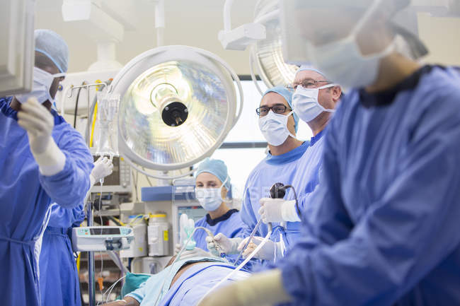 Doctors performing surgery in operating theater, looking at monitor — Stock Photo