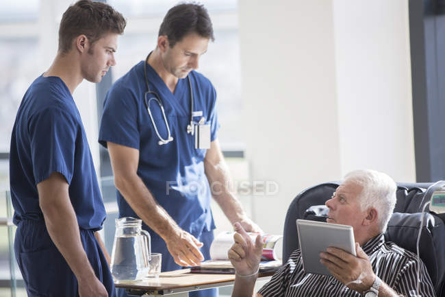 Patient using tablet pc and talking to doctors in hospital — Stock Photo