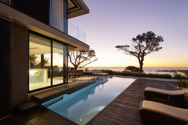 Modern luxury home showcase patio and swimming pool with sunset ocean view — Stock Photo