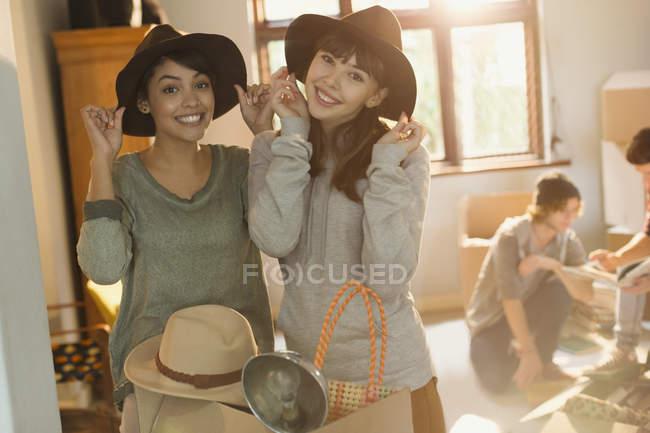 Amici delle giovani donne ritratto cercando sui cappelli muoversi in appartamento — Foto stock