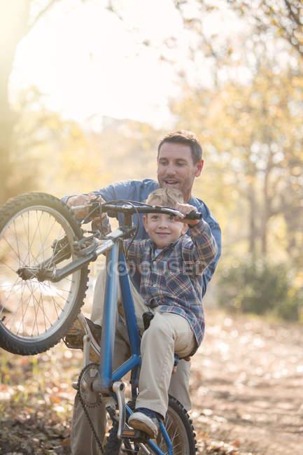 Батько, навчання сина, як робити wheelie в лісі — стокове фото