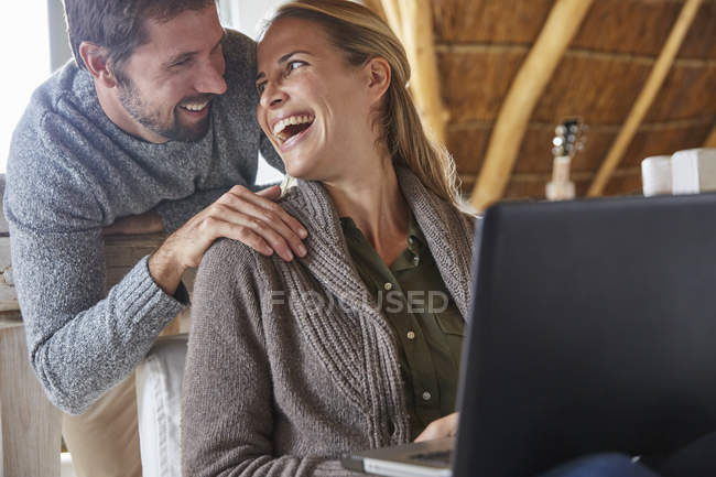 Щасливі пари сміятися і використання ноутбука — стокове фото