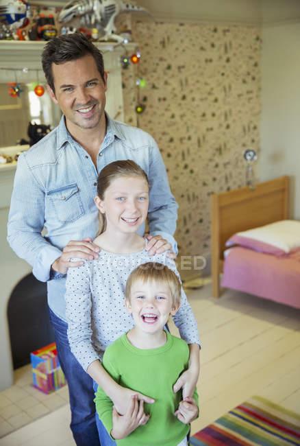 Vater und Kinder lächeln im Schlafzimmer — Stockfoto