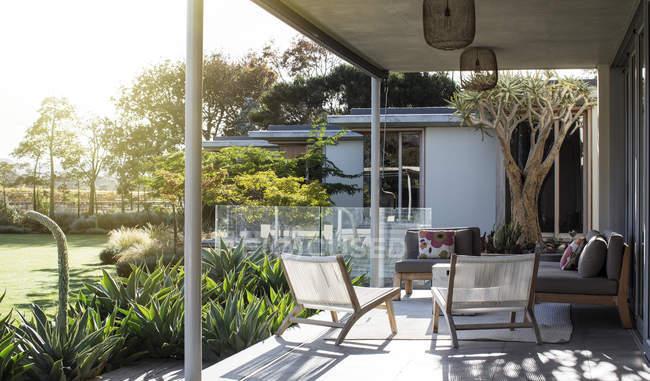 Terrasse ensoleillée avec chaises contre les plantes — Photo de stock