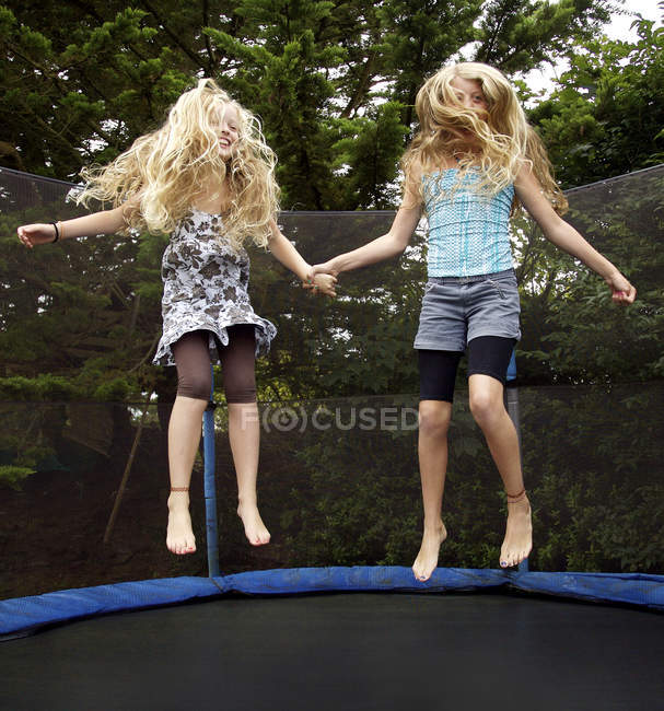 Girls jumping on trampoline outdoors — Stock Photo