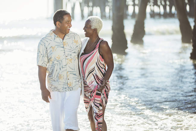 Seniorenpaar spaziert am sonnigen Strand — Stockfoto