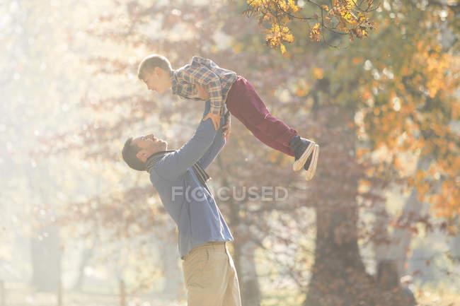 Père levant son fils au-dessus des bois avec des feuilles d'automne — Photo de stock
