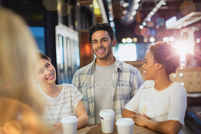 Smiling young friends drinking coffee at cafe — Stock Photo