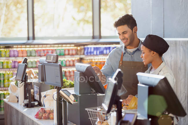 Cashiers working at grocery store checkout — Stock Photo