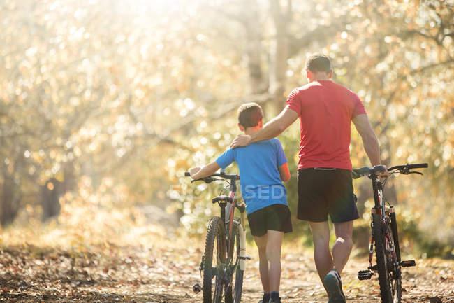 Pai afetuoso e filho andando de bicicleta de montanha no caminho na floresta — Fotografia de Stock
