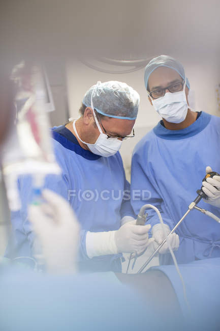 Mature doctors performing surgery and controlling liquid in saline bag — Stock Photo