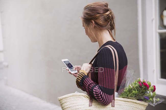 Woman video chatting with cell phone in alley — Stock Photo