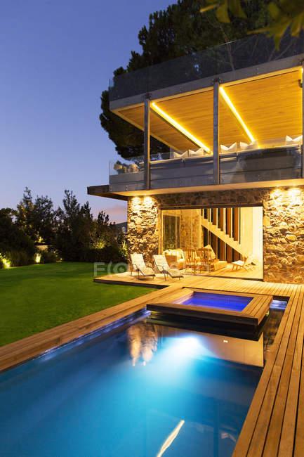 Casa moderna com vista para iluminado piscina à noite — Fotografia de Stock