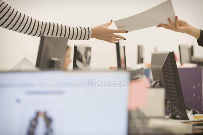 Cropped image of businesswoman handing paperwork to colleague in office — Stock Photo