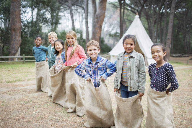 Children smiling at start of sack race — Stock Photo