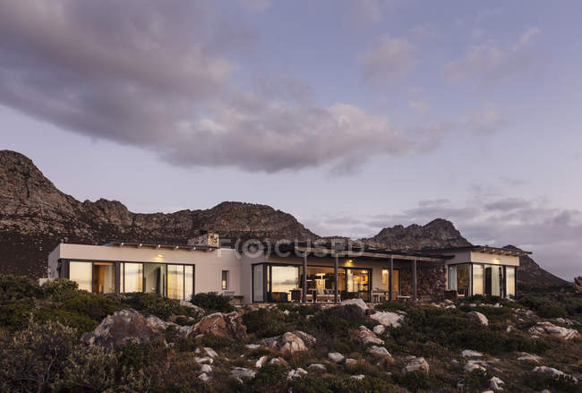Home Schaufenster außen auf schroffen Hügel unter Wolken in der Abenddämmerung — Stockfoto