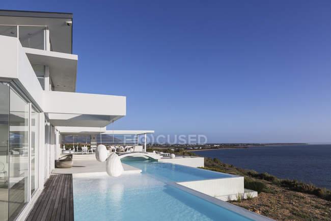 Солнечный, спокойный современный роскошный дом с бассейном и видом на океан под голубым небом — стоковое фото