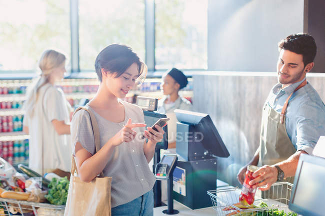 Young woman using cell phone at grocery store market checkout — Stock Photo