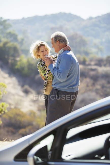 Felice coppia anziana ballare sul ciglio della strada fuori auto — Foto stock