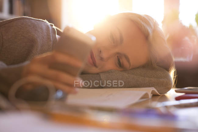 Teenage girl laying and texting with cell phone — Stock Photo