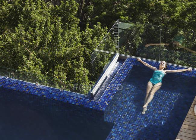 Mulher boiando na piscina de luxo — Fotografia de Stock