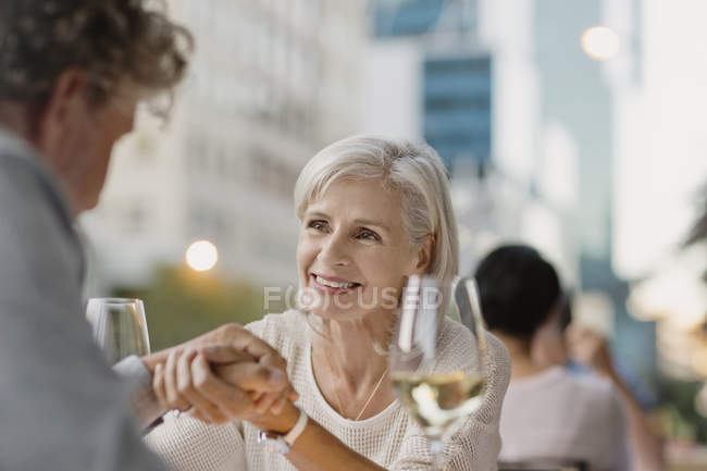 Affectionate senior couple holding hands drinking white wine at urban sidewalk cafe — Stock Photo