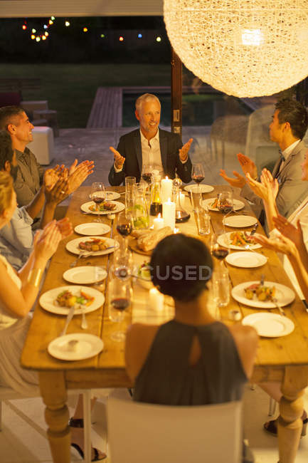 Friends applauding man at dinner party — Stock Photo