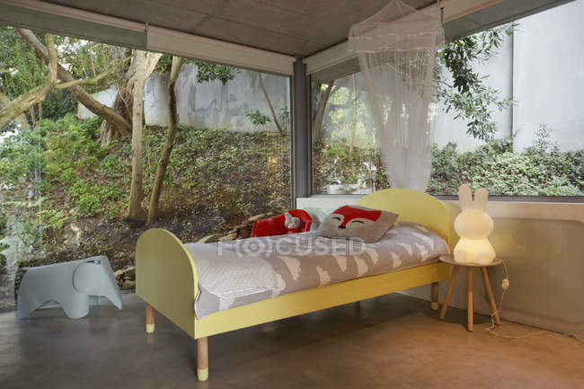 Modern luxury home showcase interior child?s bedroom surrounded by windows — Stock Photo