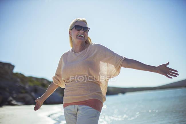 Літня жінка, посміхаючись на сонці на пляжі — стокове фото