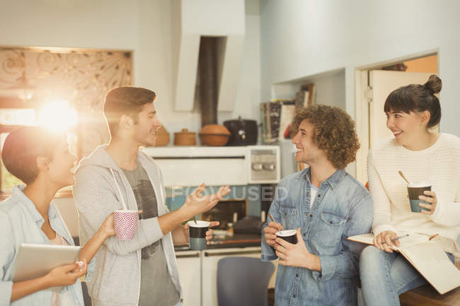 Young adults hanging out talking drinking coffee — Stock Photo
